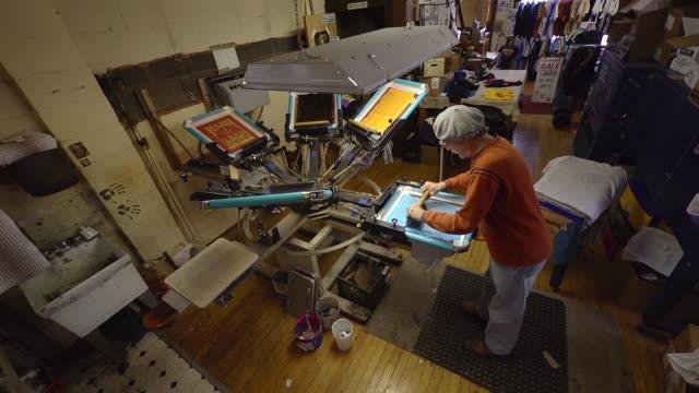 MS Shot of artisian uses a rotating silk screen press to print designs on a shirt / Ann Arbor, Michigan, United States