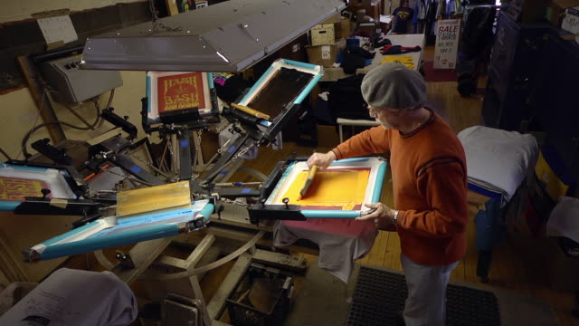 MS Shot of artisian uses a rotating silk screen press to print designs on a shirt / Ann Arbor, Michigan, United States