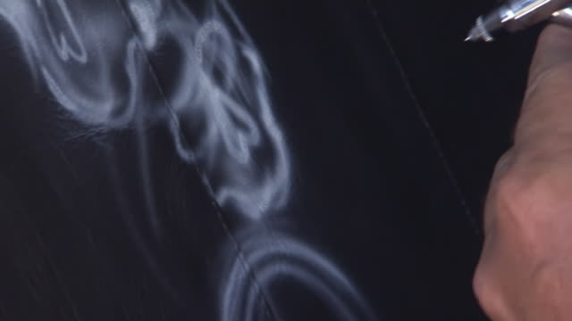 cu zo shot of artist airbrushes drawing white skull pattern on black vest during sturgis motorcycle rally / sturgis, south dakota, united states - airbrush stock videos & royalty-free footage