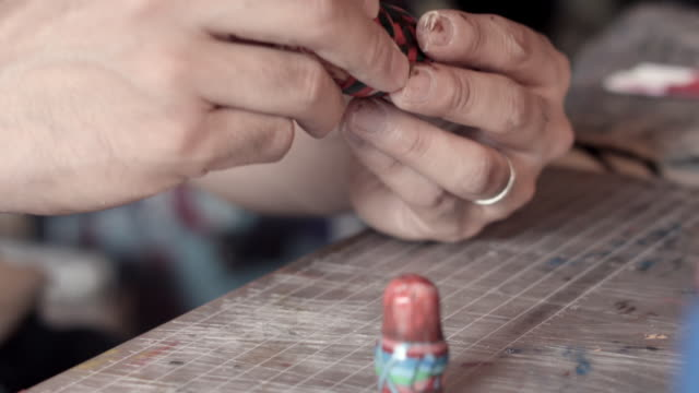 CU Shot of artist removing Matryoshka doll from one to other and placing on table / Nerima, Tokyo, Japan