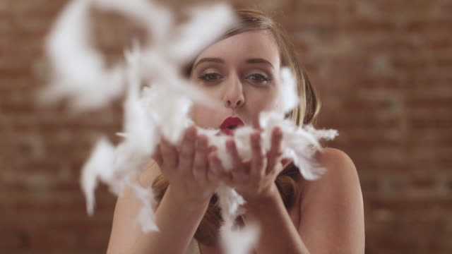 cu slo mo shot of artistic pin up girl stares raises pile of feathers and playfully blows them with smiles and laughs / portland, oregon, united states - artist's model stock videos and b-roll footage