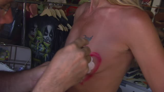 MS ZO Shot of artists airbrushes heart on woman's breast during Sturgis Motorcycle Rally / Sturgis, South Dakota, United States