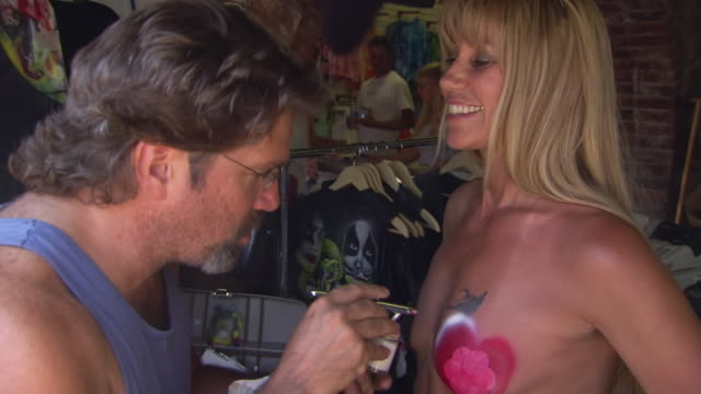vídeos y material grabado en eventos de stock de ms zi shot of artists airbrushes heart on woman's breast during sturgis motorcycle rally / sturgis, south dakota, united states - hombres desnudos