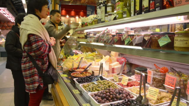 MS Shot of Asian tourists buying in delicatessen shop in Ambrogio market / Florence, Tuscany, Italy