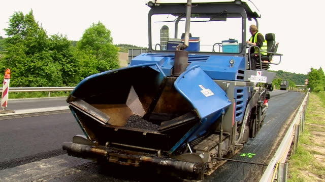ms shot of asphalt laying machine and steam roller moving on resurfacing of road / saarburg, rhineland-palatinate, germany - tarmac stock videos & royalty-free footage