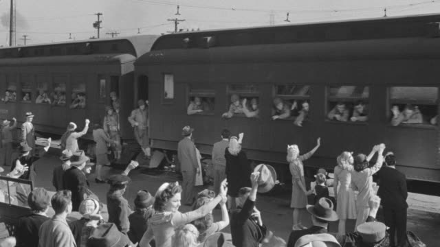 MS Shot of at train station waving to departing soldiers with marching band leads other soldiers in small parade