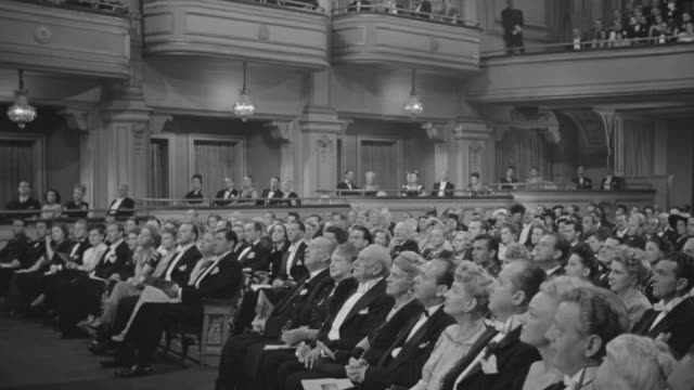 ms shot of audience in formal attire watching orchestra playing on stage - black and white stock videos & royalty-free footage