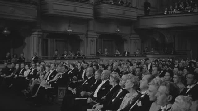 ms shot of audience in formal attire watching orchestra playing on stage - classical stock videos & royalty-free footage