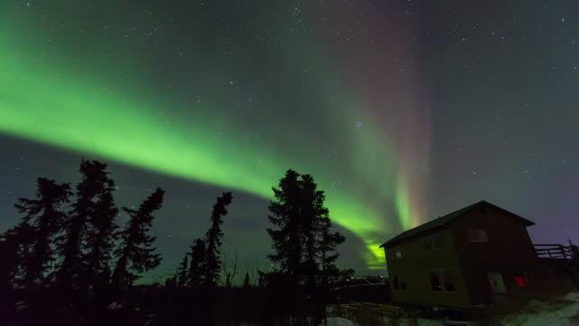 Shot of aurora polaris and a lodge at night