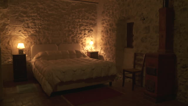 ms td shot of austere and spare bedroom in dark light / rocca calascio, abruzzo, italie - dark bedroom stock videos & royalty-free footage
