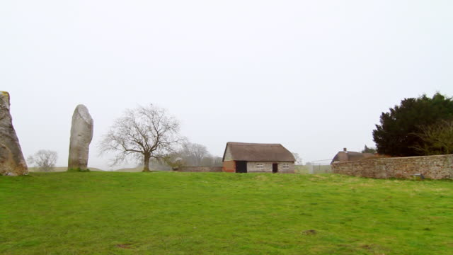 ms pan shot of avebury rocks in front of house with green landscape / wiltshire, england, united kingdom - avebury stock videos & royalty-free footage