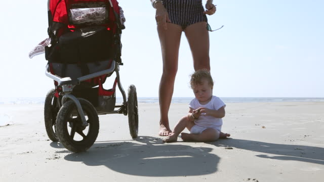 ms shot of baby boy crawling around his stroller on beach / st simon's island, georgia, united states - pushchair stock videos and b-roll footage