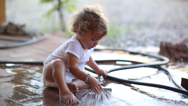 MS Shot of baby boy playing with a water hose / Santa Fe, New Mexico, United States