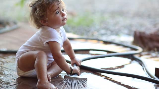 ms shot of baby boy playing with water hose / santa fe, new mexico, united states  - 男の赤ちゃん一人点の映像素材/bロール