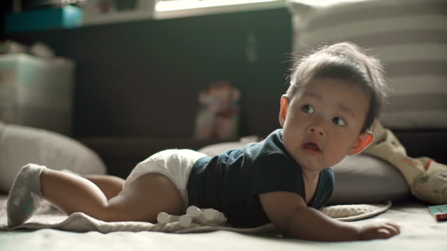 ms shot of baby boy (6-11 months) sitting up by himself - diaper stock videos & royalty-free footage