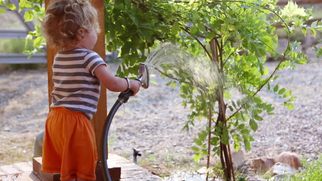 ms shot of baby boy watering the tree with a hose / santa fe, new mexico, united states  - ein männliches baby allein stock-videos und b-roll-filmmaterial