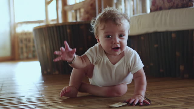 ms shot of baby playing with toy / ubud, bali, indonesia - 男の赤ちゃん一人点の映像素材/bロール