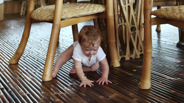 MS Shot of baby sitting under table / Ubud, Bali, Indonesia