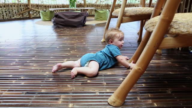 MS TU Shot of baby sitting under table / Ubud, Bali, Indonesia