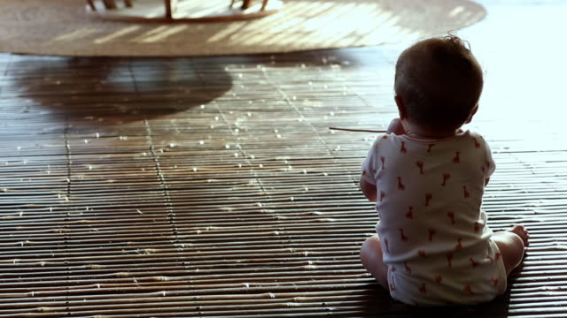 ms pan shot of baby sitting up and playing / ubud, bali, indonesia - ein männliches baby allein stock-videos und b-roll-filmmaterial