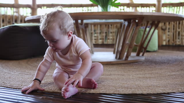 ms shot of baby sitting up by himself / ubud, bali, indonesia - strampelanzug stock-videos und b-roll-filmmaterial