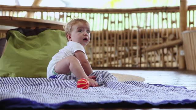 MS Shot of baby sitting up on floor / Ubud, Bali, Indonesia