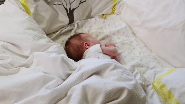 ms shot of baby sleeping in big bed / lamy, new mexico, united states - 男の赤ちゃん一人点の映像素材/bロール