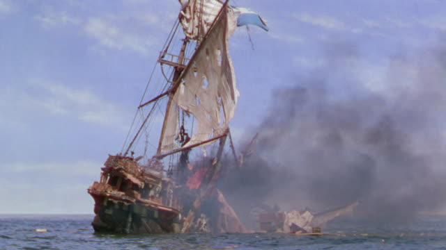 ws shot of badly damaged ship at sea, ship explodes and is on fire - nave a vela video stock e b–roll