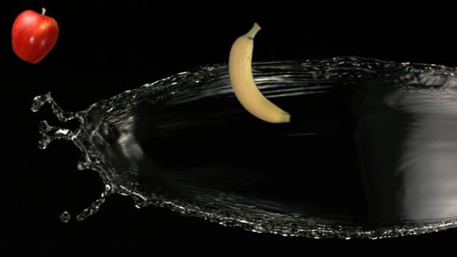 ms slo mo shot of banana,apple,lemon and water fly through air / toronto, ontario, canada  - バナナ点の映像素材/bロール