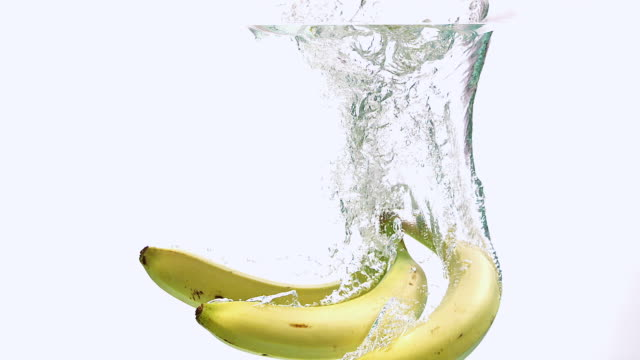 CU TD SLO MO Shot of Bananas, Fruits entering Water against White Background / Calvados, Normandy, France