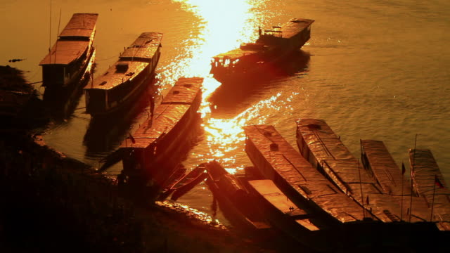 ms shot of bank of mekong river in sunset light with silhouetted slow wooden boats and people working / luang prabang, laos - travelling light stock videos & royalty-free footage