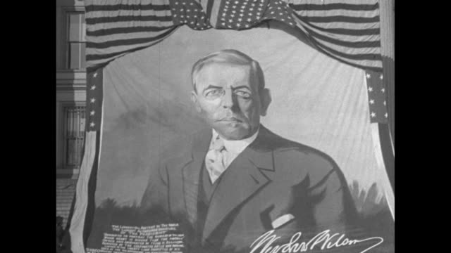 vidéos et rushes de shot of banner bearing image of woodrow wilson, and quotation from him, being placed across building entrance / wider shot of banner with people... - prohibition