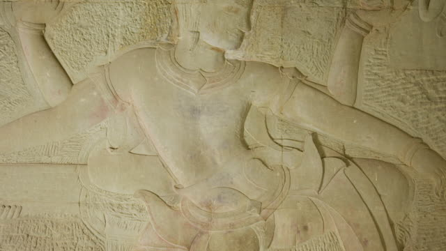 CU TU Shot of bas relief carvings of sea Churning of Milk engraving on wall of Angkor Wat Temple / Siem Reap, Siem Reap Province, Cambodia