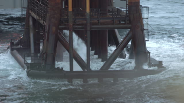 MS SLO MO Shot of base of oil rig in / The North Sea Waves are splashing around poles