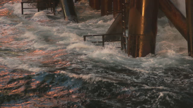 vidéos et rushes de ms slo mo shot of base of oil rig in / the north sea waves are splashing around poles  - tour de forage