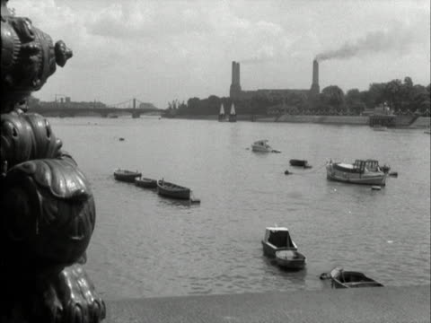 stockvideo's en b-roll-footage met shot of battersea power station taken from the north bank with moored small boats floating on the river thames in the foreground 1958 - wandsworth