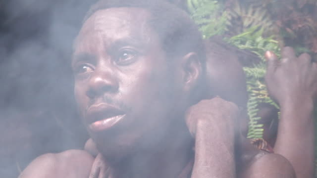 cu shot of  batwa man looking from smoke / kigez, kabale, uganda - wiese stock videos & royalty-free footage