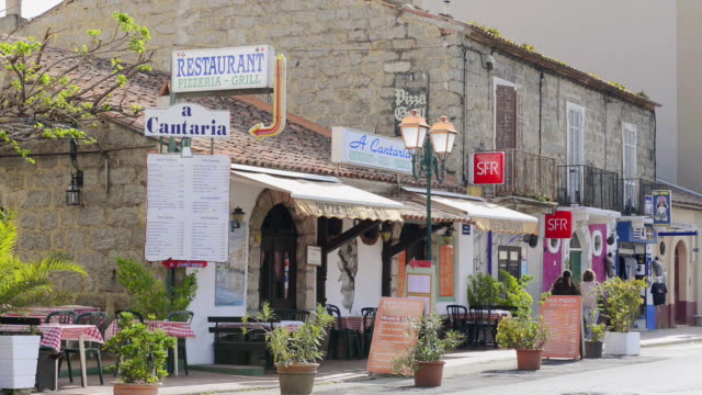 ms shot of beach road with restaurants and shops / propriano, corsica, france - 商業看板点の映像素材/bロール