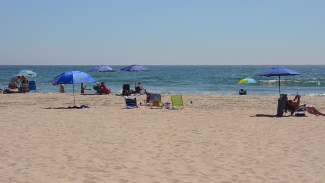 ms shot of beach with tourists and ocean near 28th street / newport beach, california, united states - 大人数点の映像素材/bロール