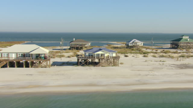 ms aerial shot of beachfront houses on stilts / dauphin island, alabama, united states - hut stock videos & royalty-free footage