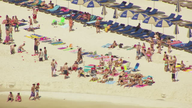 MS AERIAL Shot of beachgoers in swimming suits on beach with chairs and umbrellas and drinks / Panama City, Florida, United States