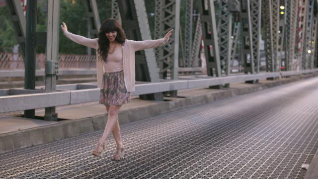 vídeos de stock e filmes b-roll de ms ts slo mo shot of beautiful brunette playfully walking along bridge while traffic drives behind her / portland, oregon, united states  - model