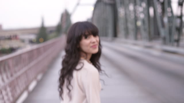 vídeos de stock, filmes e b-roll de ms pov slo mo shot of beautiful brunette playfully walking along sidewalk on bridge while holding hands with her off screen lover / portland, oregon, united states  - mulher bonita