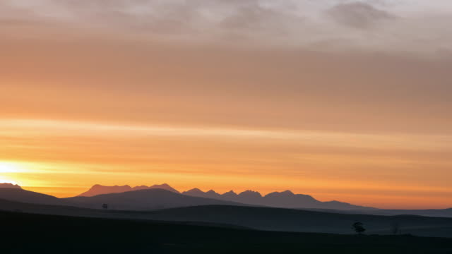 stockvideo's en b-roll-footage met ws t/l shot of beautiful clouds light up red and orange over hills with sunrise / caledon, western cape, south africa - stilstaande camera