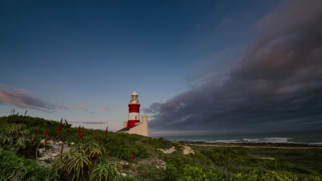 WS T/L Shot of Beautiful clouds moving over lighthouse at sunset / Agulhas, Western Cape, South Africa