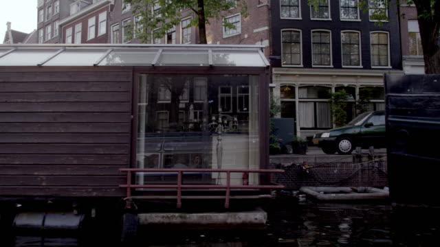 vídeos de stock e filmes b-roll de shot of beautiful houseboats on the river in amsterdam - barco casa