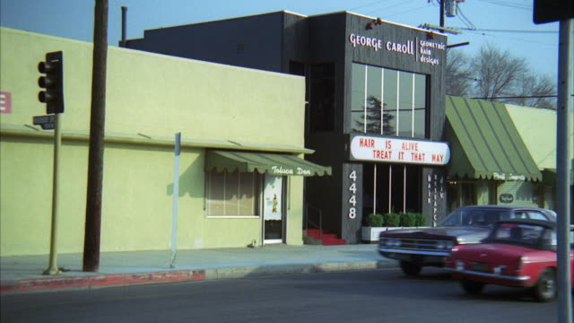ms ts shot of beauty salon and maroon 1970 ford / los angeles, california, united states - 1971年点の映像素材/bロール