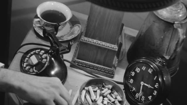 ms shot of bedside table or nightstand, on it are telephone, clock, cigarettes, ashtray  - picking up stock videos & royalty-free footage