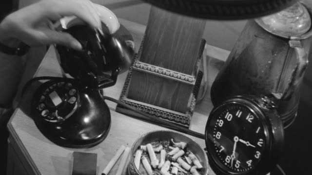 MS Shot of bedside table or nightstand, on it are telephone, clock, cigarettes, ashtray