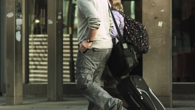 vidéos et rushes de ms ts slo mo shot of below shoulder shot of man and woman pulling suitcase in street / united kingdom - cheveux courts